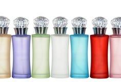 Botellas de cristal coloreadas de perfume aisladas en el fondo blanco. Fotografía de archivo libre de regalías