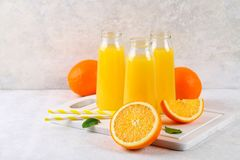 Botellas de cristal con el zumo de naranja fresco con las rebanadas anaranjadas y los tubos amarillos en una tabla gris clara Foto de archivo libre de regalías