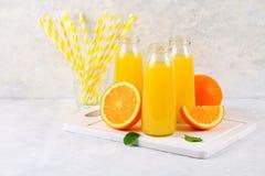 Botellas de cristal con el zumo de naranja fresco con las rebanadas anaranjadas y los tubos amarillos en una tabla gris clara Fotografía de archivo
