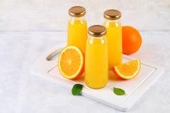 Botellas de cristal con el zumo de naranja fresco con las rebanadas anaranjadas y los tubos amarillos en una tabla gris clara Imágenes de archivo libres de regalías