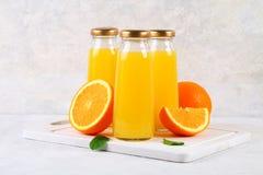 Botellas de cristal con el zumo de naranja fresco con las rebanadas anaranjadas y los tubos amarillos en una tabla gris clara Fotos de archivo