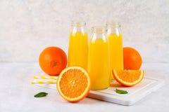 Botellas de cristal con el zumo de naranja fresco con las rebanadas anaranjadas y los tubos amarillos en una tabla gris clara Imagen de archivo libre de regalías