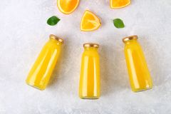 Botellas de cristal con el zumo de naranja fresco con las rebanadas anaranjadas y los tubos amarillos en una tabla gris clara Vis Foto de archivo libre de regalías