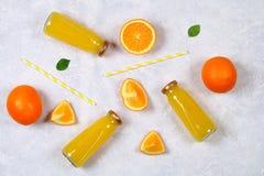 Botellas de cristal con el zumo de naranja fresco con las rebanadas anaranjadas y los tubos amarillos en una tabla gris clara Vis Imagenes de archivo