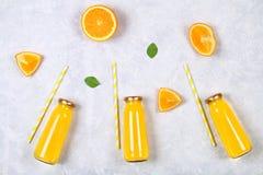 Botellas de cristal con el zumo de naranja fresco con las rebanadas anaranjadas y los tubos amarillos en una tabla gris clara Vis Fotos de archivo