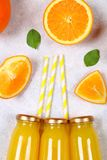 Botellas de cristal con el zumo de naranja fresco con las rebanadas anaranjadas y los tubos amarillos en una tabla gris clara Vis Imagen de archivo libre de regalías