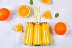 Botellas de cristal con el zumo de naranja fresco con las rebanadas anaranjadas y los tubos amarillos en una tabla gris clara Vis Imágenes de archivo libres de regalías
