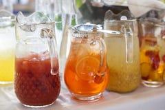 Botellas de cristal con las bebidas coloreadas en la tabla Fotografía de archivo