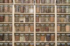 Botellas de cristal con las especias coloridas en los shelfs Foto de archivo libre de regalías