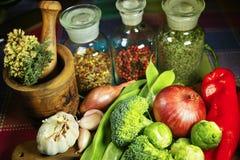 Botellas de cristal con las especias, las verduras rojas y verdes frescas, bróculi, tomates, ajo, cebolla Fotografía de archivo libre de regalías
