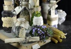 Botellas de cristal con las hierbas y las velas Foto de archivo libre de regalías