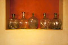 Botellas de cristal de Brown en lugar rojo en la pared amarilla Imagen de archivo libre de regalías