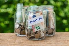 Botellas de cristal del tarro con por completo de monedas etiquetadas como educación como edu Imagenes de archivo