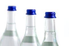 3 botellas de cristal en fila llenaron de agua de soda con la ISO de los casquillos azules Foto de archivo libre de regalías