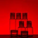 Botellas de cristal en luz roja Fotografía de archivo