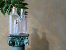 Botellas de cristal en pilar Imagen de archivo libre de regalías