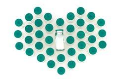 Botellas de cristal de la medicina en forma de corazón en el fondo blanco imágenes de archivo libres de regalías