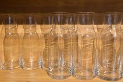 Botellas de cristal o jarros vacíos claros en la tabla de madera Fotografía de archivo