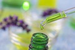 Botellas de cristal verdes con el líquido esencial de la lavanda de los descensos en dropper en fondo de madera con las flores me Imagen de archivo