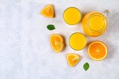Botellas de cristal, vidrios y una jarra de zumo de naranja fresco con las rebanadas de tubos anaranjados y amarillos en una tabl Fotos de archivo libres de regalías