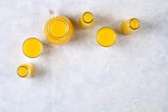 Botellas de cristal, vidrios y una jarra de zumo de naranja fresco con las rebanadas de tubos anaranjados y amarillos en una tabl Imagen de archivo