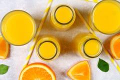 Botellas de cristal, vidrios y una jarra de zumo de naranja fresco con las rebanadas de tubos anaranjados y amarillos en una tabl Imagenes de archivo