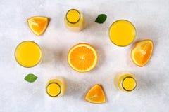 Botellas de cristal, vidrios y una jarra de zumo de naranja fresco con las rebanadas de tubos anaranjados y amarillos en una tabl Foto de archivo
