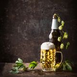 Botellas de cristal y taza de cerveza con el casquillo de la espuma y los saltos en la tabla en el fondo rústico oscuro, vista de Imagen de archivo libre de regalías