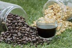 Botellas de grano de café con una taza de café Foto de archivo