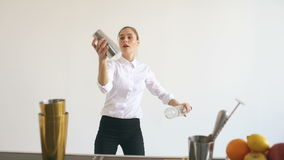 Botellas de la muchacha profesional del camarero y de la sacudida que hacen juegos malabares en la tabla móvil de la barra en el  almacen de metraje de vídeo