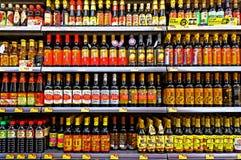 Botellas de la salsa de soja del condimento en el supermercado Imágenes de archivo libres de regalías