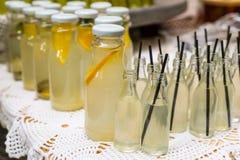 Botellas de limonada en una tabla de comida fría Foto de archivo libre de regalías