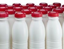 Botellas de los productos lácteos con las cubiertas brillantes imagen de archivo