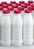 Botellas de los productos lácteos con las cubiertas brillantes foto de archivo libre de regalías