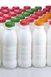 Botellas de los productos lácteos con las cubiertas brillantes fotografía de archivo