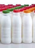 Botellas de los productos lácteos con las cubiertas brillantes imagen de archivo libre de regalías