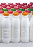 Botellas de los productos lácteos con las cubiertas brillantes imágenes de archivo libres de regalías