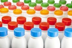 Botellas de los productos lácteos con las cubiertas brillantes imagenes de archivo