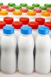 Botellas de los productos lácteos con las cubiertas brillantes fotografía de archivo libre de regalías