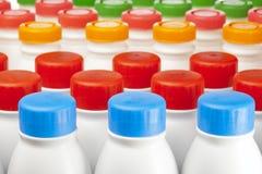Botellas de los productos lácteos con las cubiertas brillantes fotos de archivo