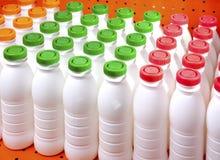 Botellas de los productos lácteos con las cubiertas brillantes en un estante en la tienda fotos de archivo libres de regalías
