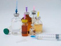 Botellas de medicina y de una jeringuilla grande Imagenes de archivo