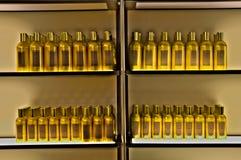 Botellas de oro en fila en un estante imagen de archivo libre de regalías