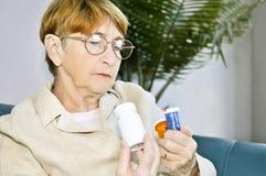 Botellas de píldora mayores de la lectura de la mujer Fotos de archivo