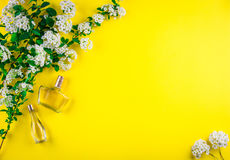 Botellas de perfume con las flores imagenes de archivo