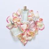 Botellas de perfume con los pétalos de la flor en fondo ligero Perfumería, colección de la fragancia Accesorios de las mujeres fotografía de archivo libre de regalías
