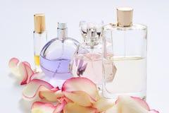 Botellas de perfume con los pétalos de la flor en fondo ligero Perfumería, colección de la fragancia Accesorios de las mujeres imagen de archivo libre de regalías