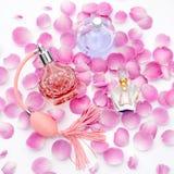 Botellas de perfume con los pétalos de la flor en el fondo blanco Perfumería, cosméticos, colección de la fragancia imagen de archivo libre de regalías
