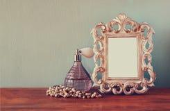Botellas de perfume del antigue del vintage con el viejo marco, en la tabla de madera imagen filtrada retra Imagenes de archivo