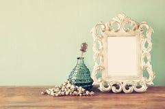 Botellas de perfume del antigue del vintage con el viejo marco, en la tabla de madera imagen filtrada retra Fotos de archivo